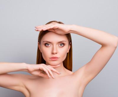 Eine Kinnkorrektur kann auch mit Fillern erfolgen. - Schöne Frau hält Hand unter ihr Kinn und andere Hand auf Ihre Stirn und schaut direkt in die Kamera.