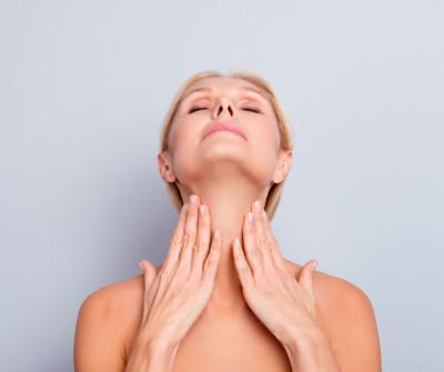 Kinn im Mittelpunkt, Frau schaut mit geschlossen Augen nach oben und streicht über ihren Hals